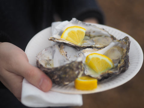Three oysters with lemon slices on them