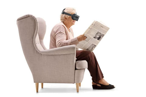 Elderly woman sitting on couch and reading newspaper with Vision Buddy