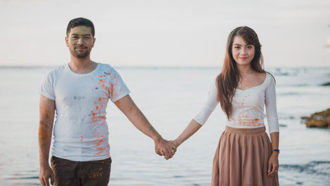 Man and woman holding hands on the beach looking at camera