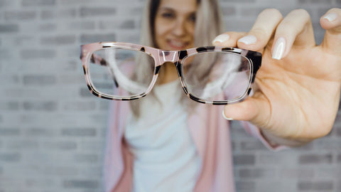 A woman holding pink glasses close to the camera. Give someone with Low Vision a New Beginning with Vision Buddy!