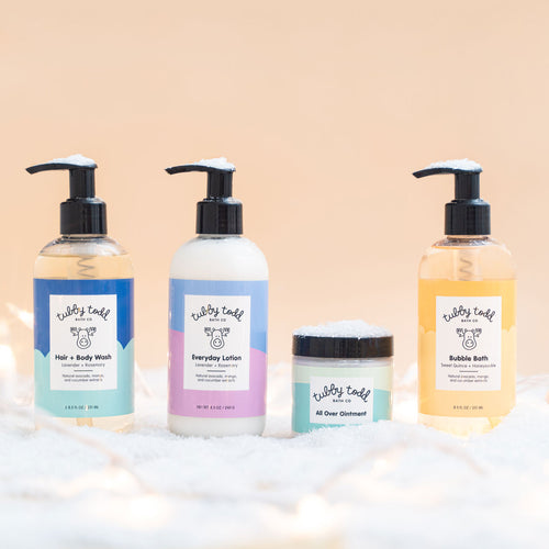 The Essentials Gift Set on snow with cream background and lights