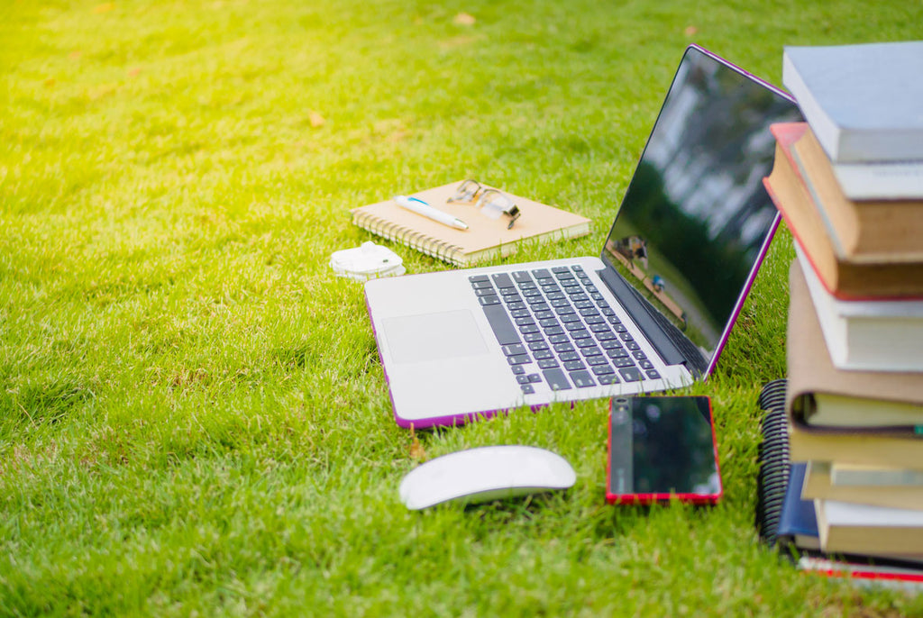 A laptop and a pile of books and school supplies sit on outdoor grass waiting for an AHS student attending summer institute