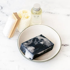 activated charcoal exfoliating athletic soap on soap dish for athletic women