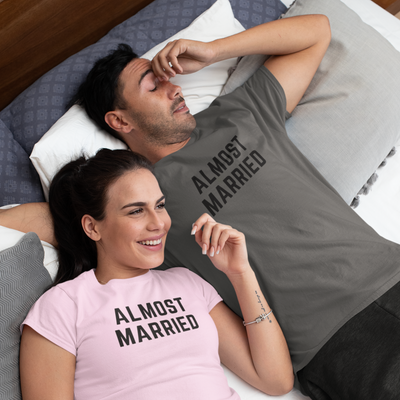 Man and woman lay in bed. Woman is smiling, man is pinching the bridge of his nose. Both are wearing shirts that say Almost Married.