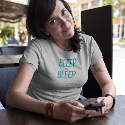 Woman at table holding phone with head tilted wearing a shirt that says Bleep That Bleep