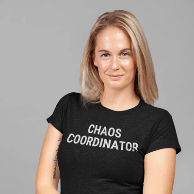 Blonde woman staring right at camera standing with arms gathered in front of her wearing Chaos Coordinator shirt