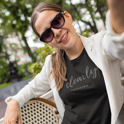 Woman wearing a ponytail, sunglasses and blazer taking a selfie