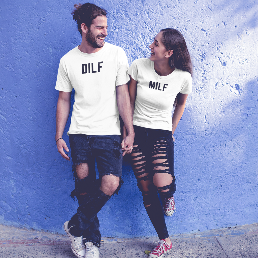 Good looking man and woman couple holding hands, wearing holey jeans and leaning up against a periwinkle wall