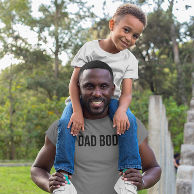 Smiling dad with son sitting on his shoulders outside
