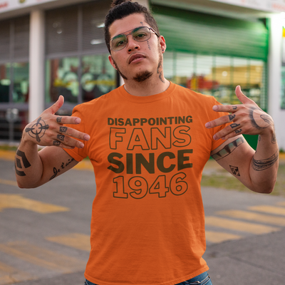Man wearing glasses with lots of tattoos and a shirt that says Disappointing Fans Since 1946.