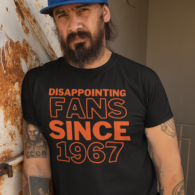 Serious looking bearded man leaning up against a rusty wall with sleeve tattoos