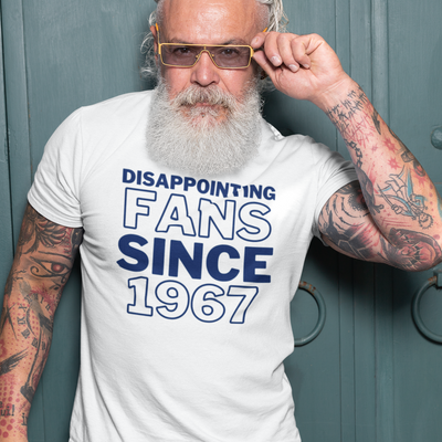 Older tattooed man with gray hair and beard holding glasses