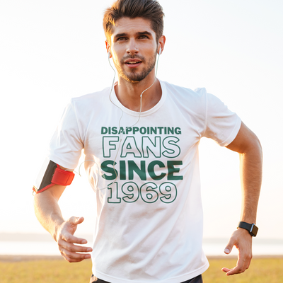 Man running with headphones on wearing a shirt that says Disappointing Fans Since 1969