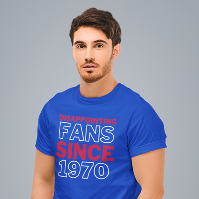 Handsome bearded man looks right at the camera while wearing a Disappointing Fans Since 1970 shirt.
