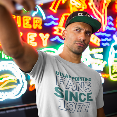 Man with stern face and a baseball cap takes a selfie of himself in front of a neon-lit wall.