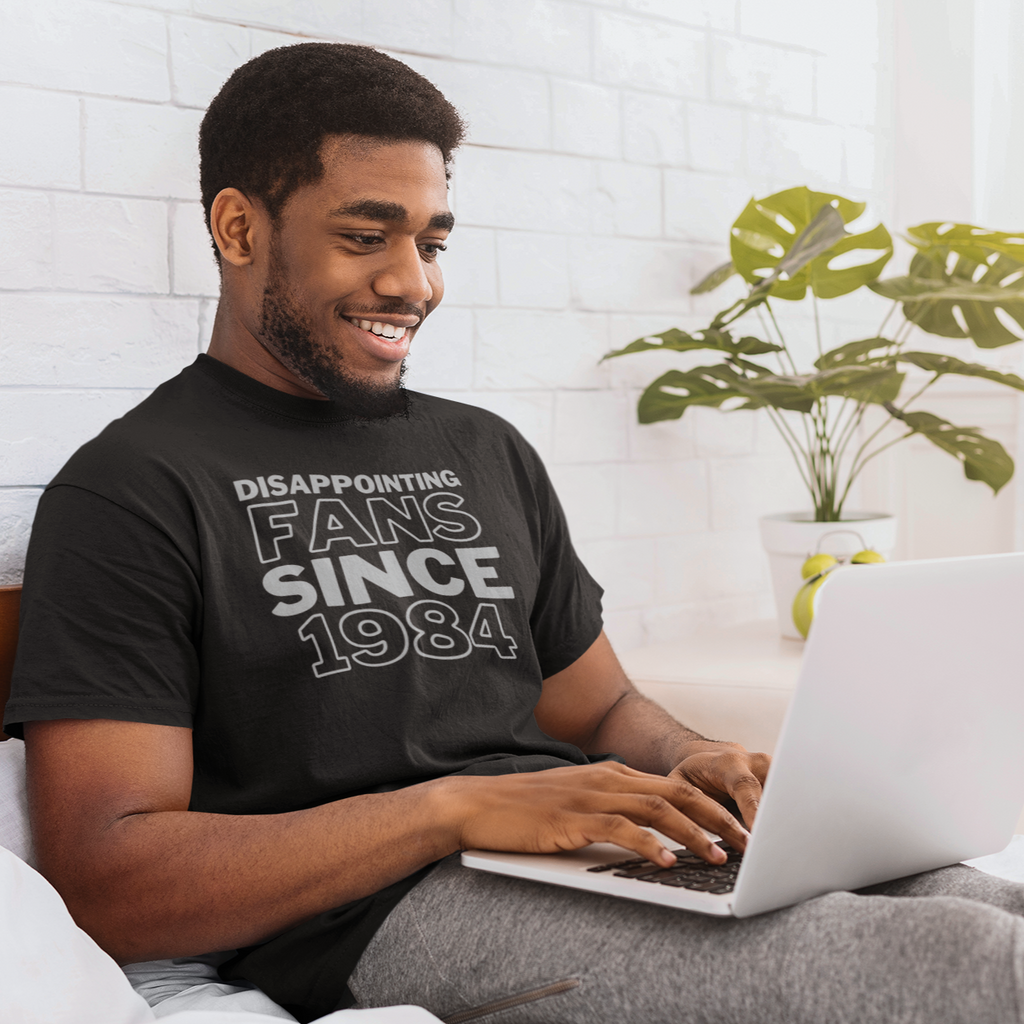Smiling man sitting in bed typing on his laptop