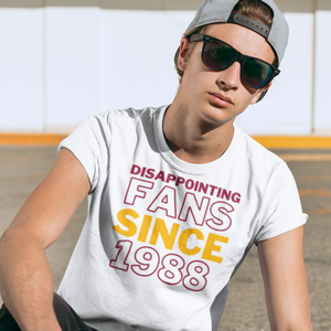 Young man with backwards hat, sunglasses and serious face wearing a shirt that says Disappointing Fans Since 1988.