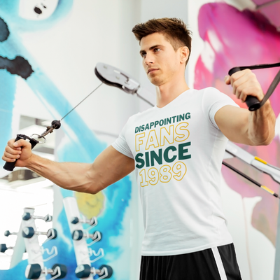 Handsome man working out on a cable machine at the gym in front of a colorful wall.