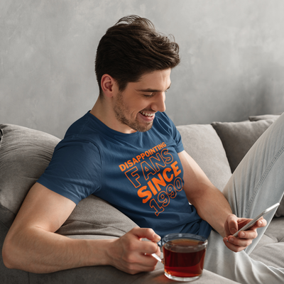 Smiling man holding a cup of tea looks down at his phone while sitting on the couch
