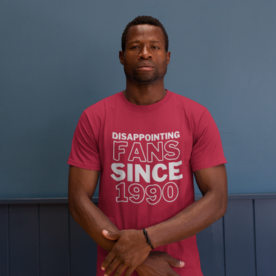 Man with blank look on his face stands in front of a blue wall wearing a shirt that says Disappointing Fans Since 1990 from brazenginger.com.