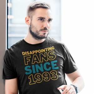 Sad man with stubble looking off into the distance while wearing a shirt that says Disappointing Fans Since 1993.