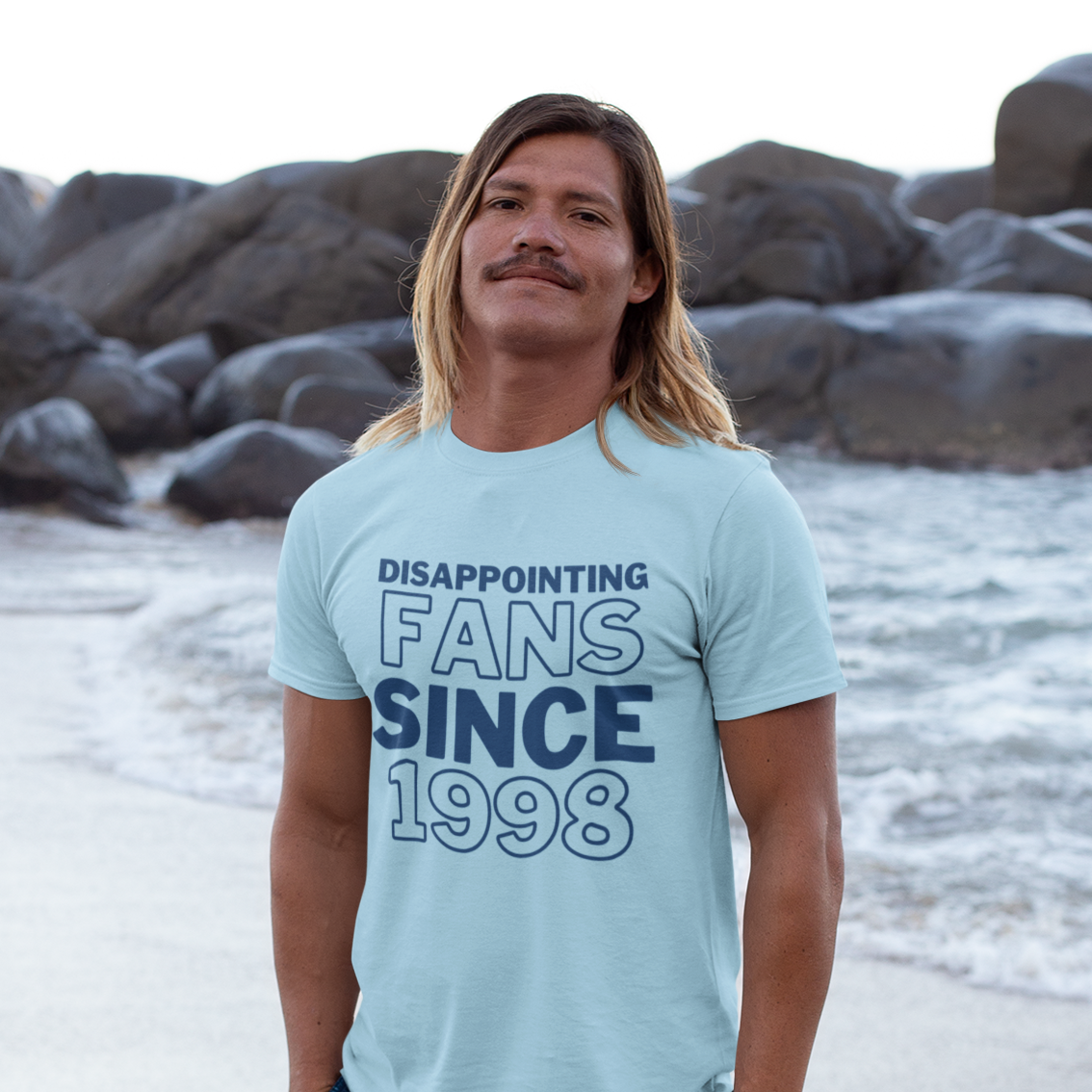 Tanned man with long hair and moustache stands on the shore with water and large rocks in the background.
