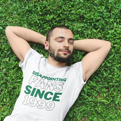 Man lays in grass with arms behind his head and eyes closed