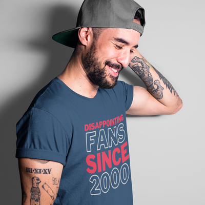 Handsome, smiling, bearded man with sleeve tattoos and a backwards hat stands sideways and looks down