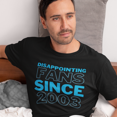 Man with combover looks off into the distance while sitting in bed and wearing a shirt that says Disappointing Fans Since 2003 from brazenginger.com.
