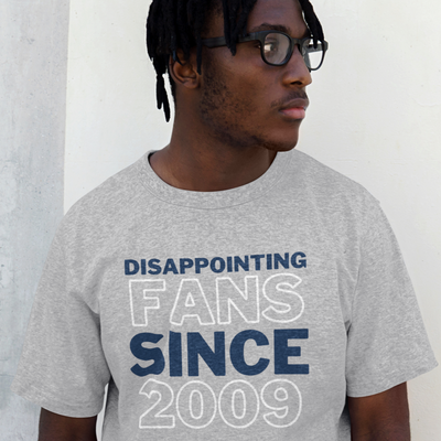 Man with short dreds and glasses looks off to the side while wearing a shirt that says Disappointing Fans Since 2009 from brazenginger.com.