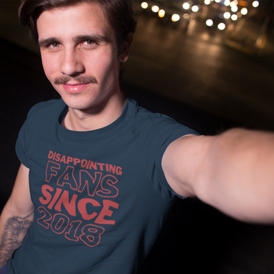 Young man with dark hair and a moustache takes a selfie of himself at night.