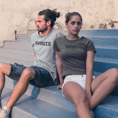 Angry looking male and female couple sits outside on blue concrete steps wearing matching shirts that say Divorced.