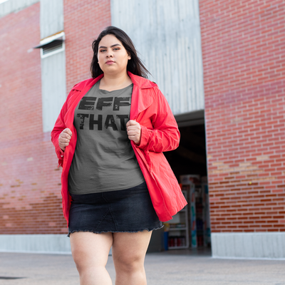 Plus size dark haired woman wearing a red jacket and black denim skirt outside a brick building