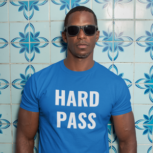 Serious man wearing dark sunglasses stands in front of a mural tiled wall wearing a Hard Pass shirt