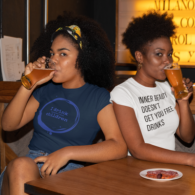 Two women sitting in a bar drinking beer