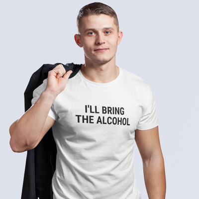 Handsome young man holding coat over shoulder wearing a shirt that says I'll Bring The Alcohol