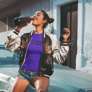 Woman leaning on an old car in front of old buildings drinking a bottle of wine