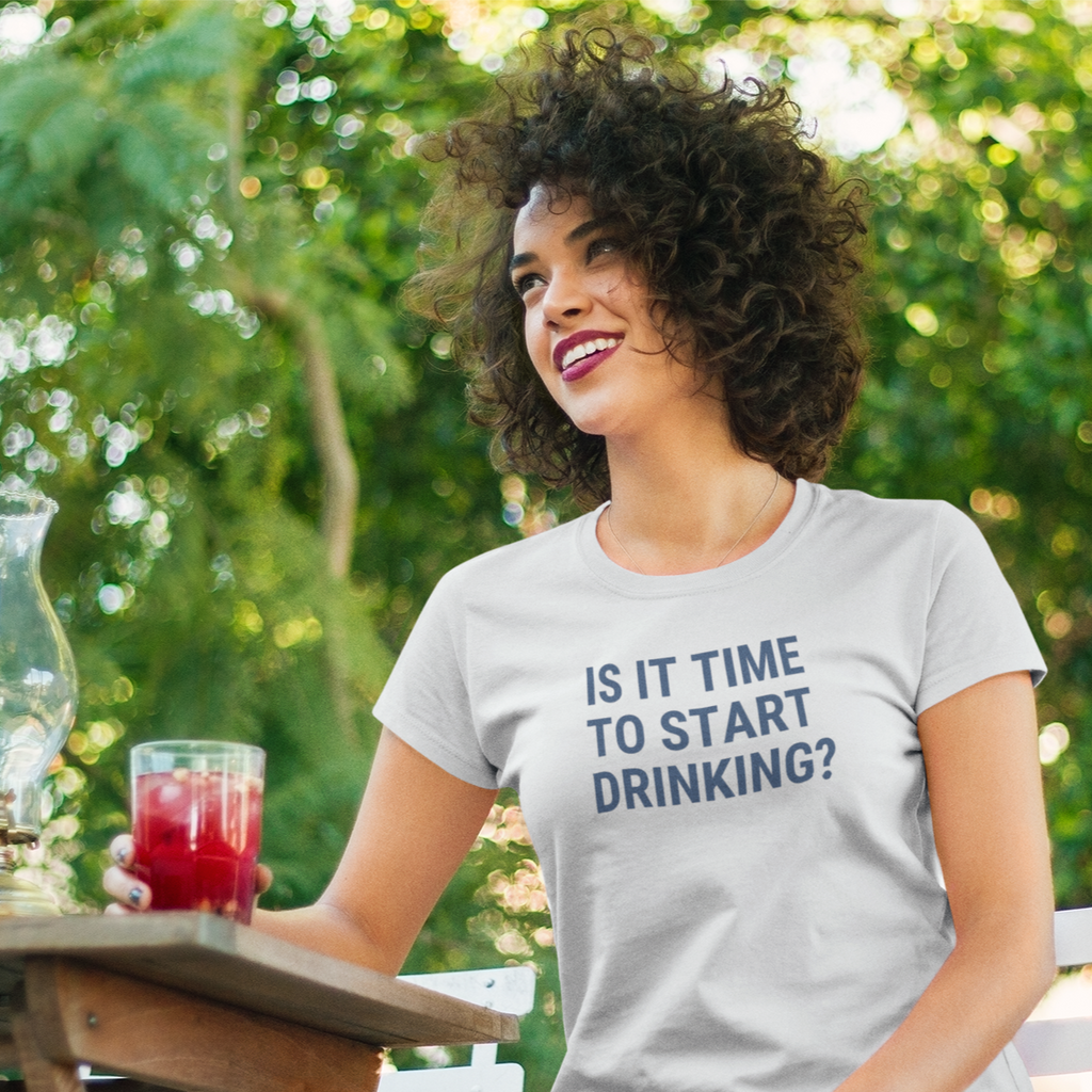 Curly dark haired woman smiling while outside holding a red beverage with a shirt that says Is It Time To Start Drinking?
