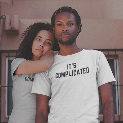 Young woman leans over young man's shoulder while both are wearing shirts that say It's Complicated.