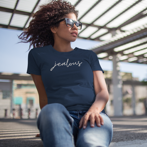 Woman with dark curly hair and sunglasses sitting on a stair outside looking off in the distance wearing a Jealous shirt