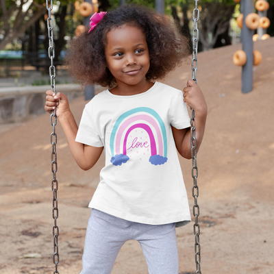 Little girl stands on a swing with a pink bow in her hair and a sassy smirk on her face while wearing a shirt with a rainbow that says Love on it.