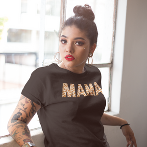 Woman with high bun, red lips and tattoos leaning up against a window wearing a Mama shirt in giraffe print