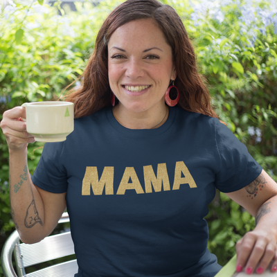 Woman smiling and holding a coffee cup wearing a Mama in Gold Glitter Print Shirt