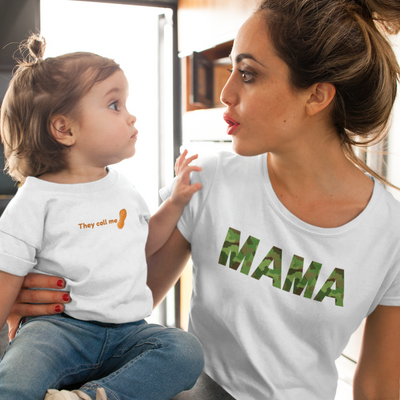 Woman wearing a Mama shirt with her arm around a toddler girl while looking at each other