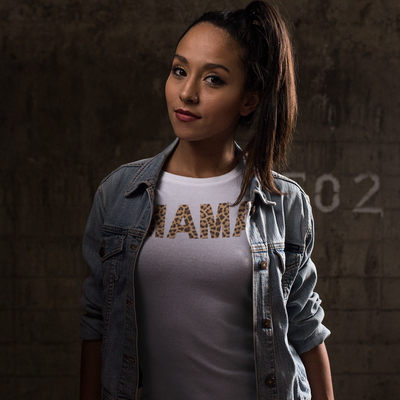 Woman with a high ponytail in front of a cement block wall in a darkened room wearing a jean jacket and Mama in leopard shirt