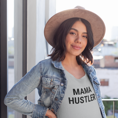 Woman with dark hair under a tan hat and a jean jacket with a Mama Hustler shirt on