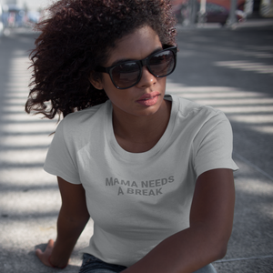 Woman with black kinky hair and sunglasses sits outside with a shirt that says Mama Needs A Break