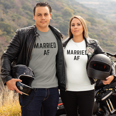 Man and woman holding helmets stand in front of their motorcycle looking right at the camera with neutral expressions