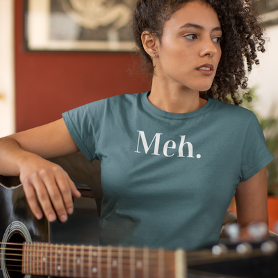 Woman with dark curly hair looking off to the side wearing a Meh shirt