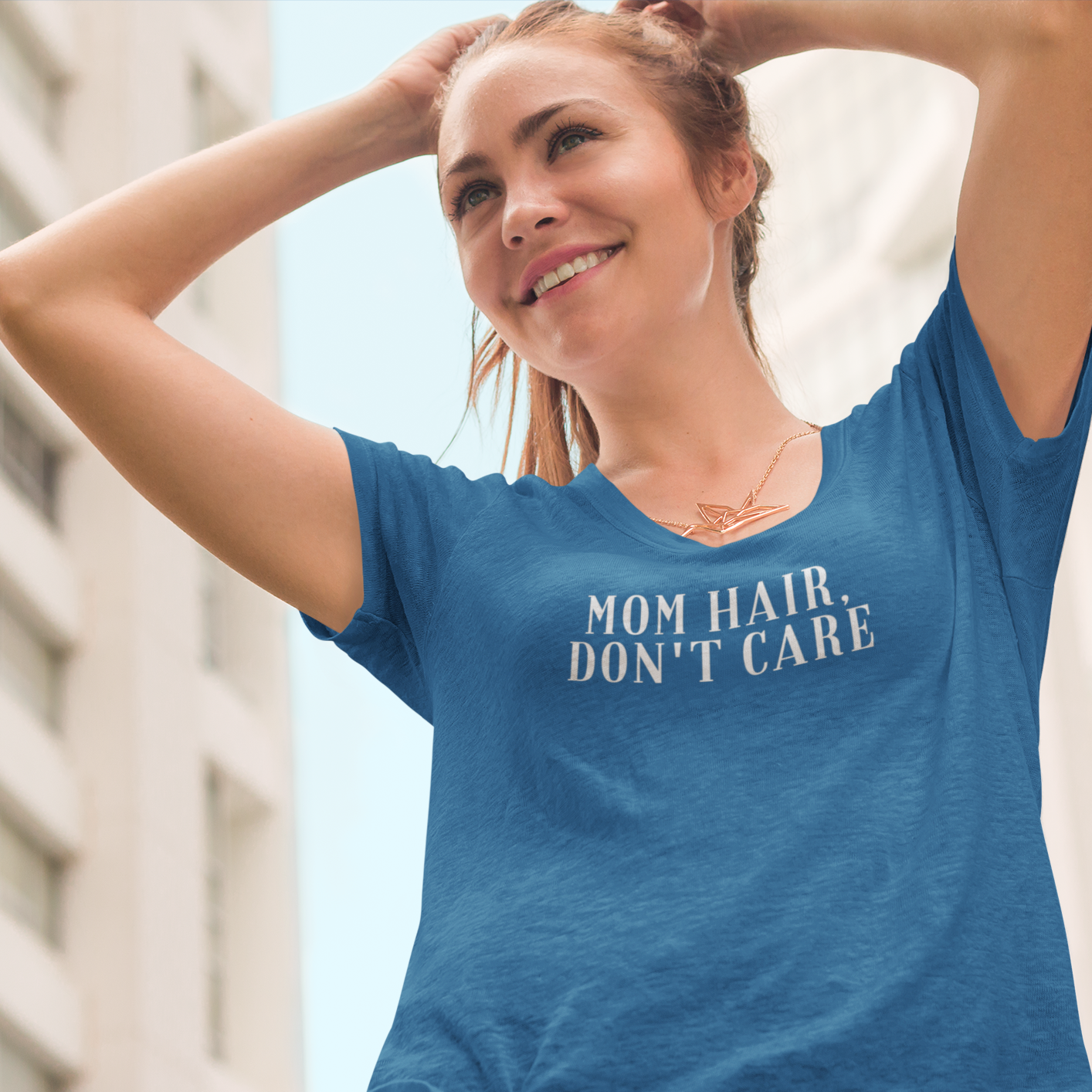 Smiling woman with city in the background fixing her ponytail wearing a Mom Hair, Don't Care shirt